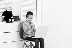 Fille de sourire avec l'ordinateur portable dirigeant le doigt photo stock