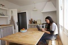 Fille de sourire avec l'ordinateur portable, lisant le message au téléphone dans la cuisine Image stock