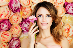 Fille de sourire avec la fleur sur le fond de fleur Mode MOIS de femme Photographie stock
