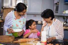 Fille de sourire avec la mère et la grand-mère préparant la nourriture dans la cuisine Photo libre de droits