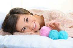 Fille de sourire avec le fil de laine pour le tricotage Photographie stock