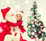 Fille de sourire avec le père noël et le cadeau à la maison Photographie stock