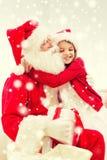 Fille de sourire avec le père noël et le cadeau à la maison Image stock