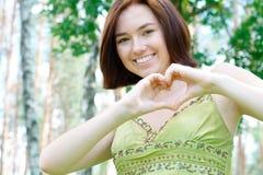 Fille de sourire avec un signe de coeur Photographie stock libre de droits