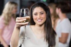 Fille de sourire ayant un verre de vin avec ses amis Photos stock