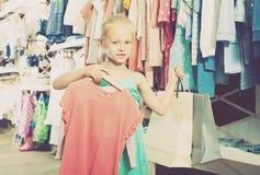 Fille de sourire chez la boutique de vêtements des enfants Photographie stock libre de droits