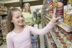 Fille de sourire choisissant des produits de l'étagère de supermarché images libres de droits