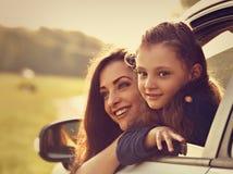 Fille de sourire de déplacement heureuse de mère et d'enfant regardant du nouveau