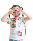 Fille de sourire d'enfant regardant par les mains peintes Images stock