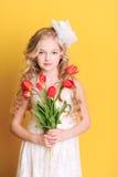 Fille de sourire d'enfant tenant des fleurs sur le jaune Image stock