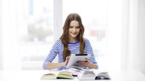 Fille de sourire d'étudiant avec le PC et les livres de comprimé banque de vidéos