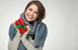 Fille de sourire dans l'écharpe d'hiver tenant le cadeau rouge Grand sourire avec le te Image libre de droits