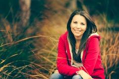Fille de sourire dans l'herbe grande images stock