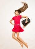 Fille de sourire dans la robe rouge et le sac à main posant sur le plancher Photo libre de droits