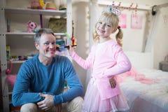 Fille de sourire dans le costume féerique mettant le maquillage sur son visage de pères Photographie stock libre de droits