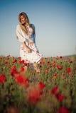 Fille de sourire dans le domaine des fleurs photographie stock
