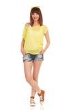 Fille de sourire dans les shorts de jeans et le dessus jaune Photos stock