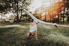 Fille de sourire dans les vêtements de sport faisant le yoga en parc photographie stock libre de droits
