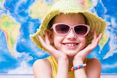 Fille de sourire dans un chapeau et des lunettes de soleil sur le fond de la carte du monde photographie stock