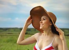 Fille de sourire de brunette dans le chapeau en jour d'été Photographie stock libre de droits