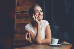 Fille de sourire de hippie appelant avec le téléphone de cellules tout en détendant après marche dans le jour d'été Photographie stock