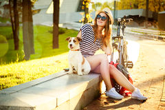 Fille de sourire de hippie avec son chien et vélo Photographie stock
