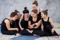 Fille de sourire de yogi s'exerçant, ayant une coupure à la classe, groupe d'amis observant au téléphone Photographie stock