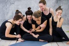 Fille de sourire de yogi s'exerçant, ayant une coupure à la classe, groupe d'amis observant au téléphone Images libres de droits