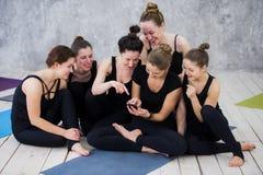 Fille de sourire de yogi s'exerçant, ayant une coupure à la classe, groupe d'amis observant au téléphone Image libre de droits