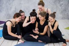 Fille de sourire de yogi s'exerçant, ayant une coupure à la classe, groupe d'amis observant au téléphone Photo libre de droits