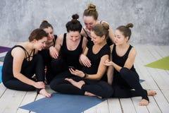 Fille de sourire de yogi s'exerçant, ayant une coupure à la classe, groupe d'amis observant au téléphone Photographie stock libre de droits