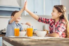 Fille de sourire donnant un top-là à son frère Photo stock