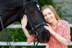 Fille de sourire embrassant le cheval photographie stock