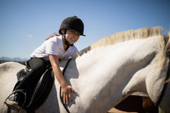Fille de sourire embrassant le cheval blanc dans le ranch Photos stock