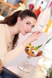 Fille de sourire en café mangeant une crème glacée  Image stock