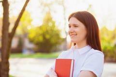 Fille de sourire enthousiaste d'étudiant tenant dehors un livre rouge photo libre de droits