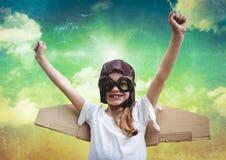 Fille de sourire feignant pour être un pilote sur le fond de ciel nuageux Photo stock
