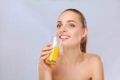 Fille de sourire gaie avec la serviette tenant un verre de jus d'orange Photos stock