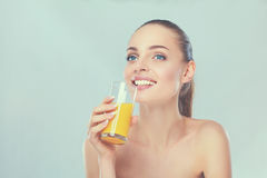 Fille de sourire gaie avec la serviette tenant un verre de jus d'orange Image stock