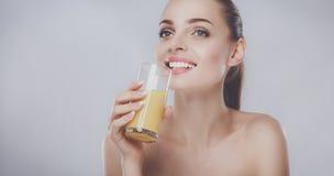 Fille de sourire gaie avec la serviette tenant un verre de jus d'orange Photographie stock libre de droits