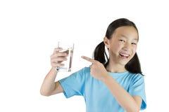 Fille de sourire, gril asiatique jugeant un verre de l'eau d'isolement sur le whi image stock