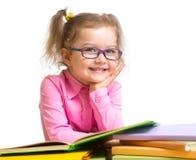 Fille de sourire heureuse d'enfant dans des livres de lecture en verre Photographie stock