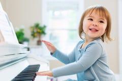 Fille de sourire heureuse d'enfant en bas âge jouant le piano Photo stock