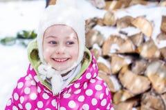 Fille de sourire heureuse d'enfant regardant la neige extérieure pendant l'hiver Photo libre de droits
