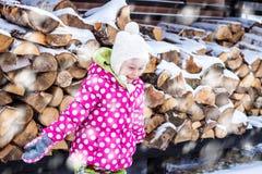 Fille de sourire heureuse d'enfant regardant la neige extérieure pendant l'hiver Photographie stock