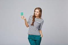 Fille de sourire heureuse dans les vêtements décontractés, montrant la carte de crédit en blanc Photographie stock libre de droits