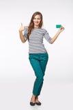 Fille de sourire heureuse dans les vêtements décontractés, montrant la carte de crédit en blanc Image stock