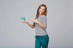 Fille de sourire heureuse dans les vêtements décontractés, montrant la carte de crédit en blanc Photos stock