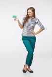Fille de sourire heureuse dans les vêtements décontractés, montrant la carte de crédit en blanc Photographie stock