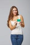 Fille de sourire heureuse dans les vêtements décontractés, montrant la carte de crédit en blanc Images stock